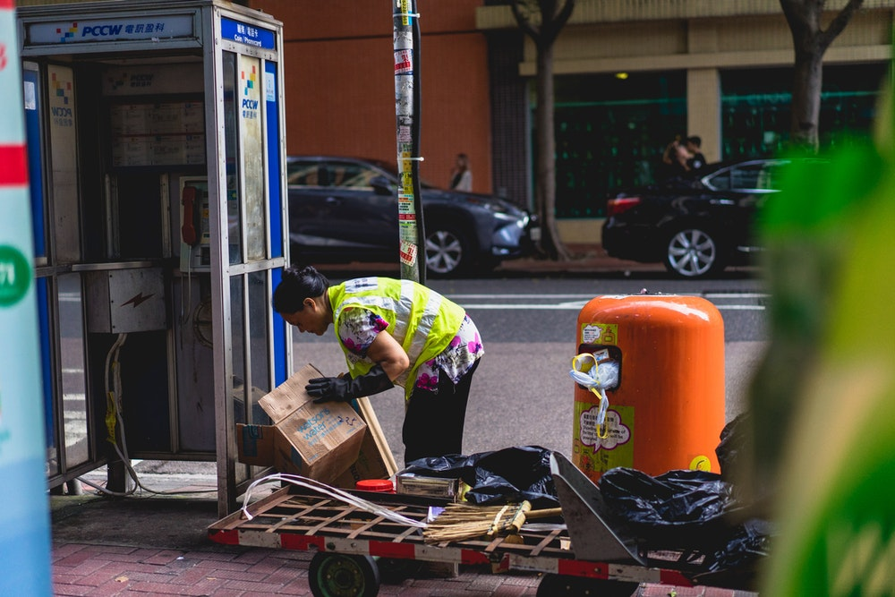Hong Kong city worker breaking down a box
