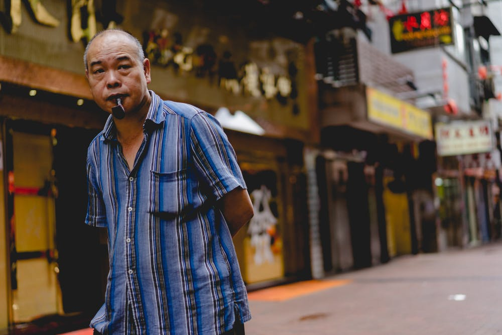 Man looking in the distance smoking a pipe in Hong Kong