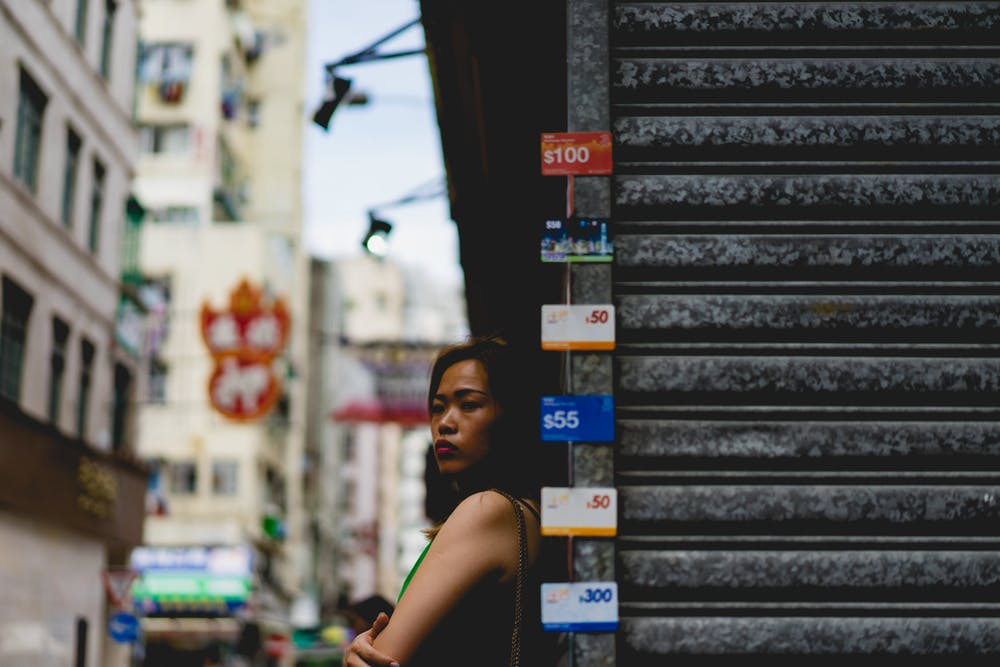 Girl looking to the side of a metal store front in Hong Kong