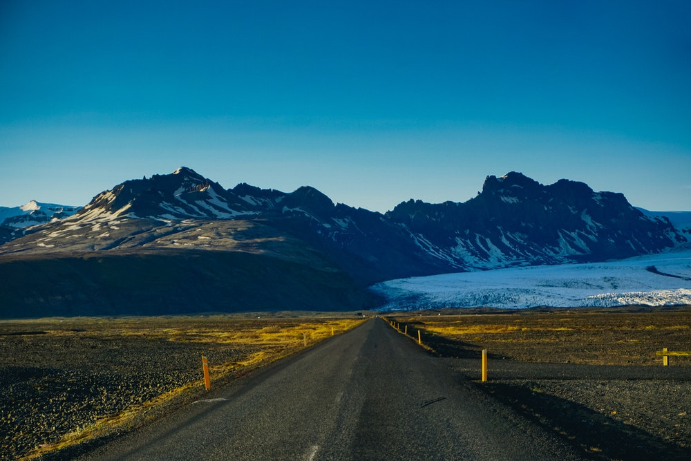 Iceland's scenery is like nowhere else. Its mountains are pristine, its waterfalls are clear, its geysers explode and its piercing blue skies create a backdrop for snow-capped peaks. The roads are unique and look like they are straight out of a postcard.