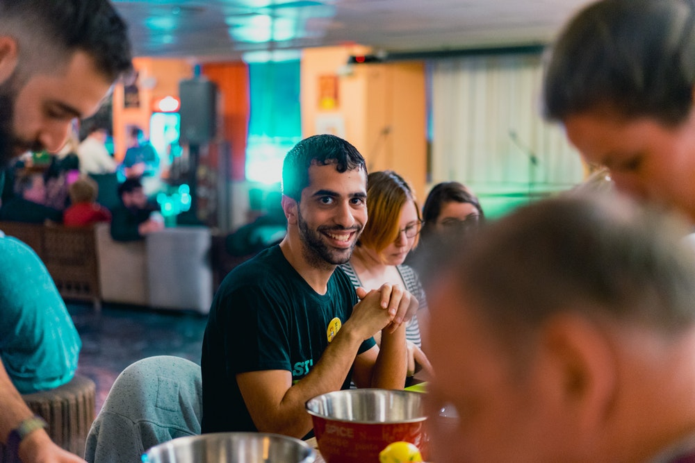 Our new friend smiling because he is making hummus at Abraham Hostel in Jerusalem