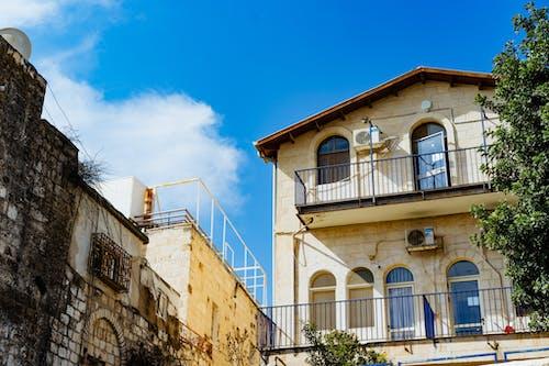 Siyah metal balkonları ve mavi gökyüzü olan bir evin yanında eski Kudüs beyaz taş şehir duvarları