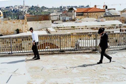 İki adam Kudüs Eski Şehir'de taş bir çatıda yürüyor