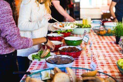 Kırmızı ve beyaz kareli masa örtüsüyle bir masada ekmek ve İsrail salatası alan iki kadın