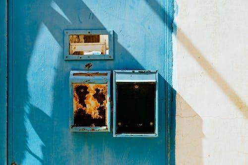 Beyaz bir duvarın yanında paslı dikey posta kutuları olan parlak mavi boyalı kapı