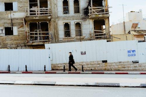 Kudüs'te beyaz barikatlarla dolu bir caddede yürüyen adam