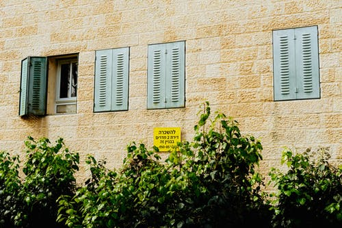 Pencerelerinde açık mavi metal panjurlu Kudüs beyaz taş bina