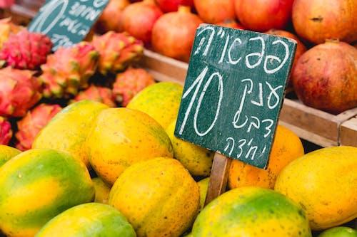 İsrail pazarındaki bir meyve tezgahında beyaz yazılı İbranice tabela