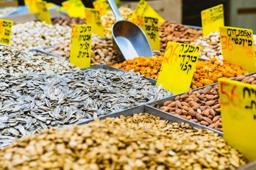 Bir pazarda ayçiçeği tohumları ve fındık için siyah İbranice yazılı sarı işaretler