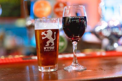 Bar tezgahında bir bardak bira ve bir bardak kırmızı şarap