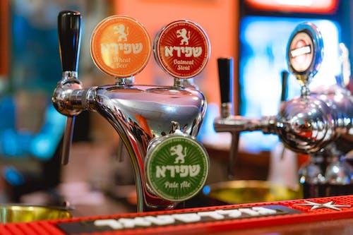 Bir bar tezgahında İbranice kırmızı, sarı ve yeşil bira isimleri