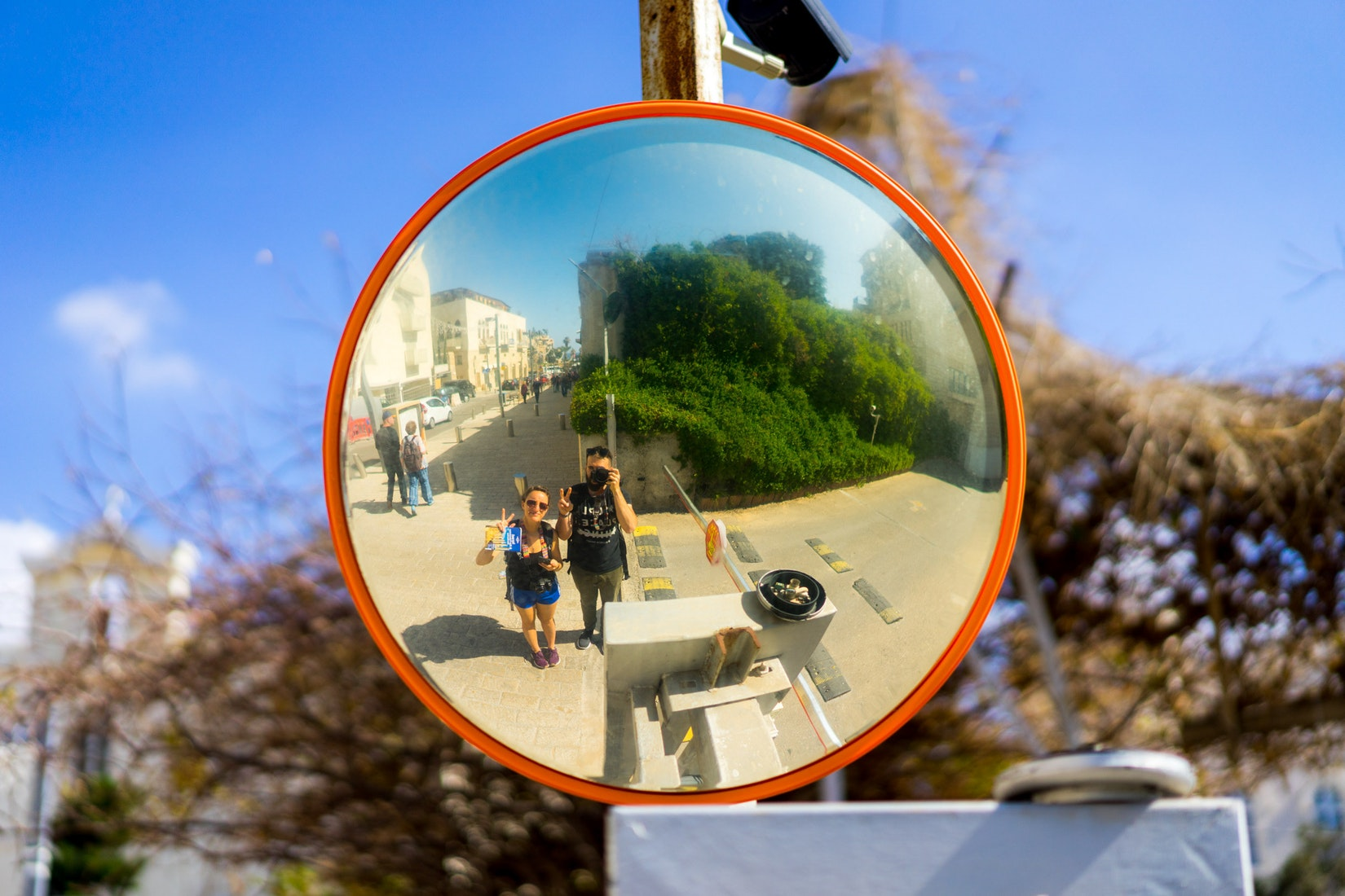 Becca and Dan taking a reflection selfie in a traffic mirror in Jaffa, Israel