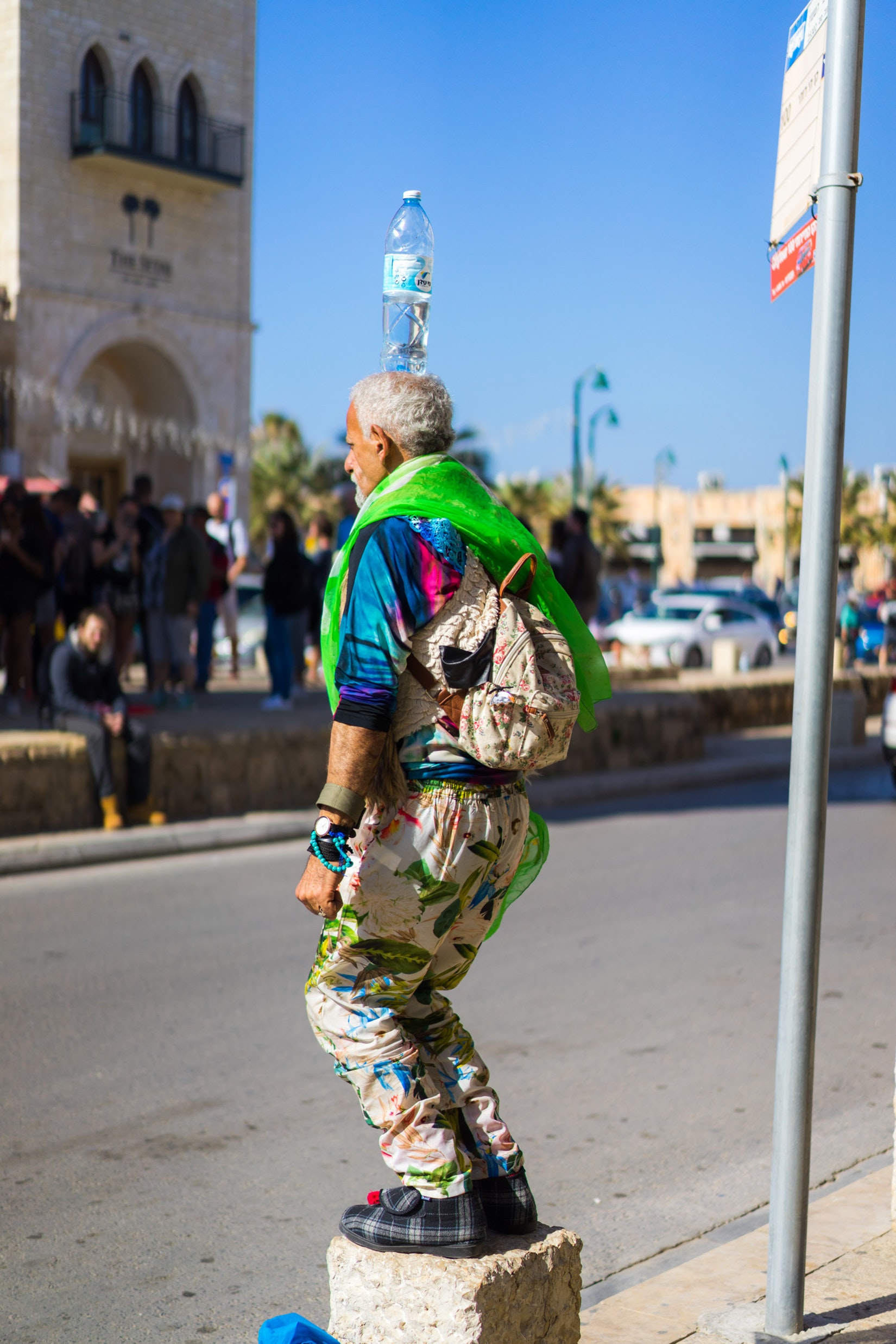 A street-performing man balancing a bottle on his head in Jaffa, Israel
