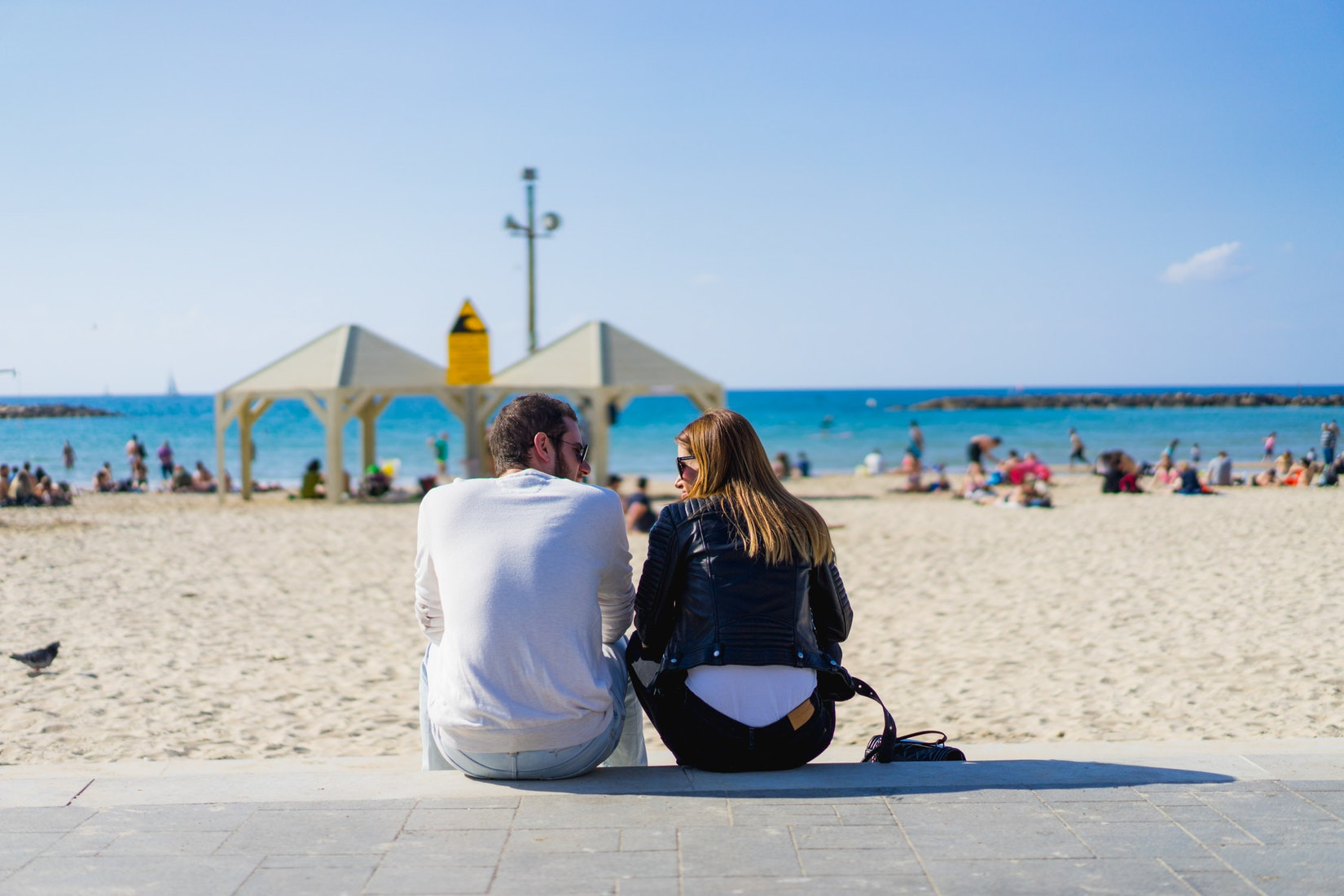 A couple sitting on the beach in Tel Aviv, Israel