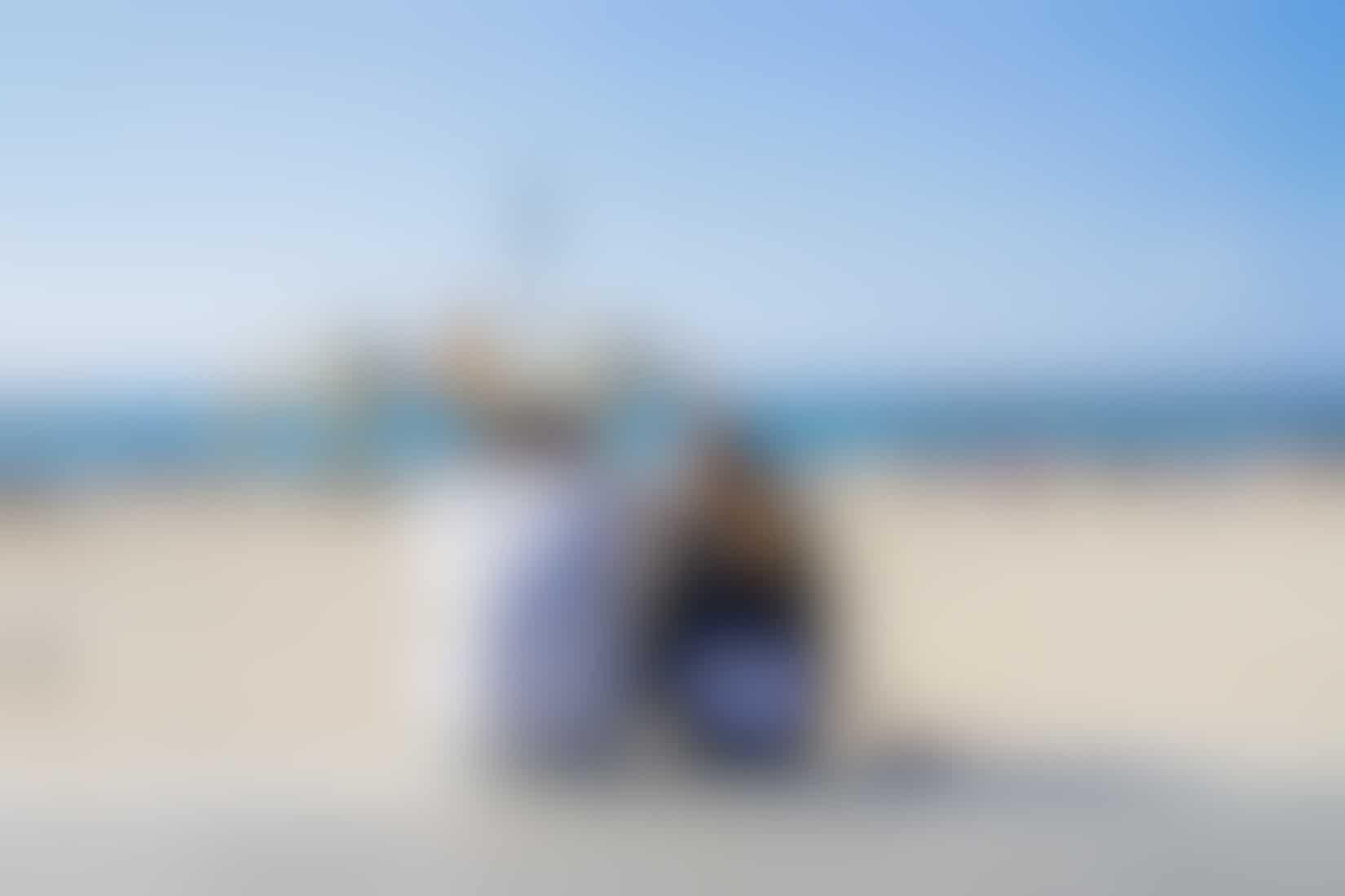 A couple sitting on the beach in Tel Aviv, Israel