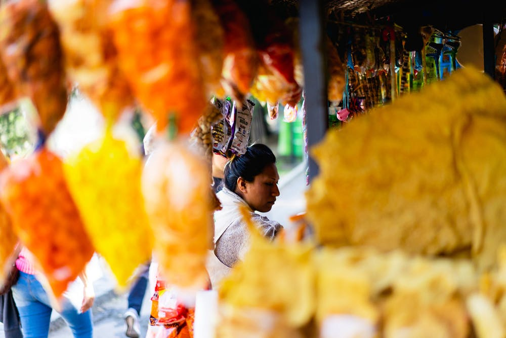 Female street vendor seen through rows of Mexican street snacks at a Mexico City market