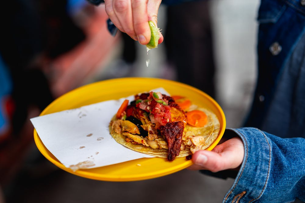 Girl squeezing a lime onto a rotisserie chicken taco on a plastic plate outside a Mexico City market
