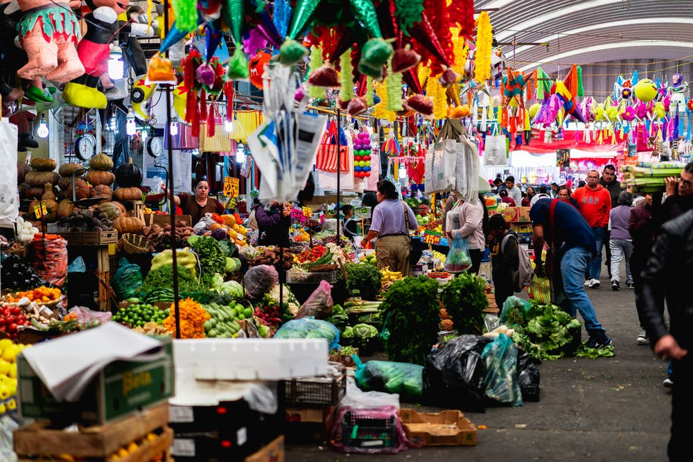 Market vendors selling produce, fruits and vegetables next to pinatas at one of Mexico City's largest market