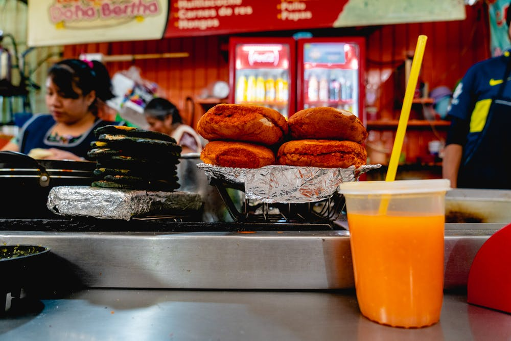 Fresh orange juice in a plastic cup in front of hot buns at a vendor stall in a Mexico City market