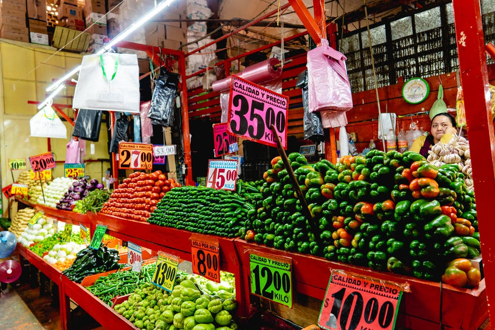 Vendors selling rows of fresh chayote, peppers, cucumbers, tomates and chiles inside a big Mexico City market