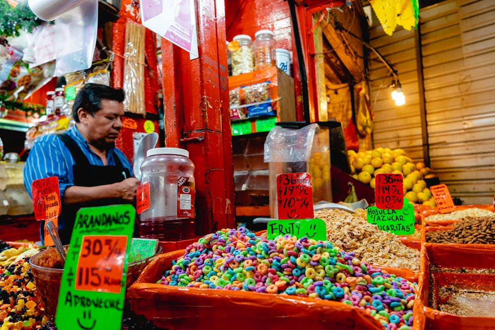 Vendor stall selling fruity dry cereals for purchase inside a large Mexico City market