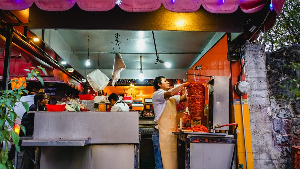 Mexican man cutting meat from a trompo to make tacos al pastor in a Mexico City market