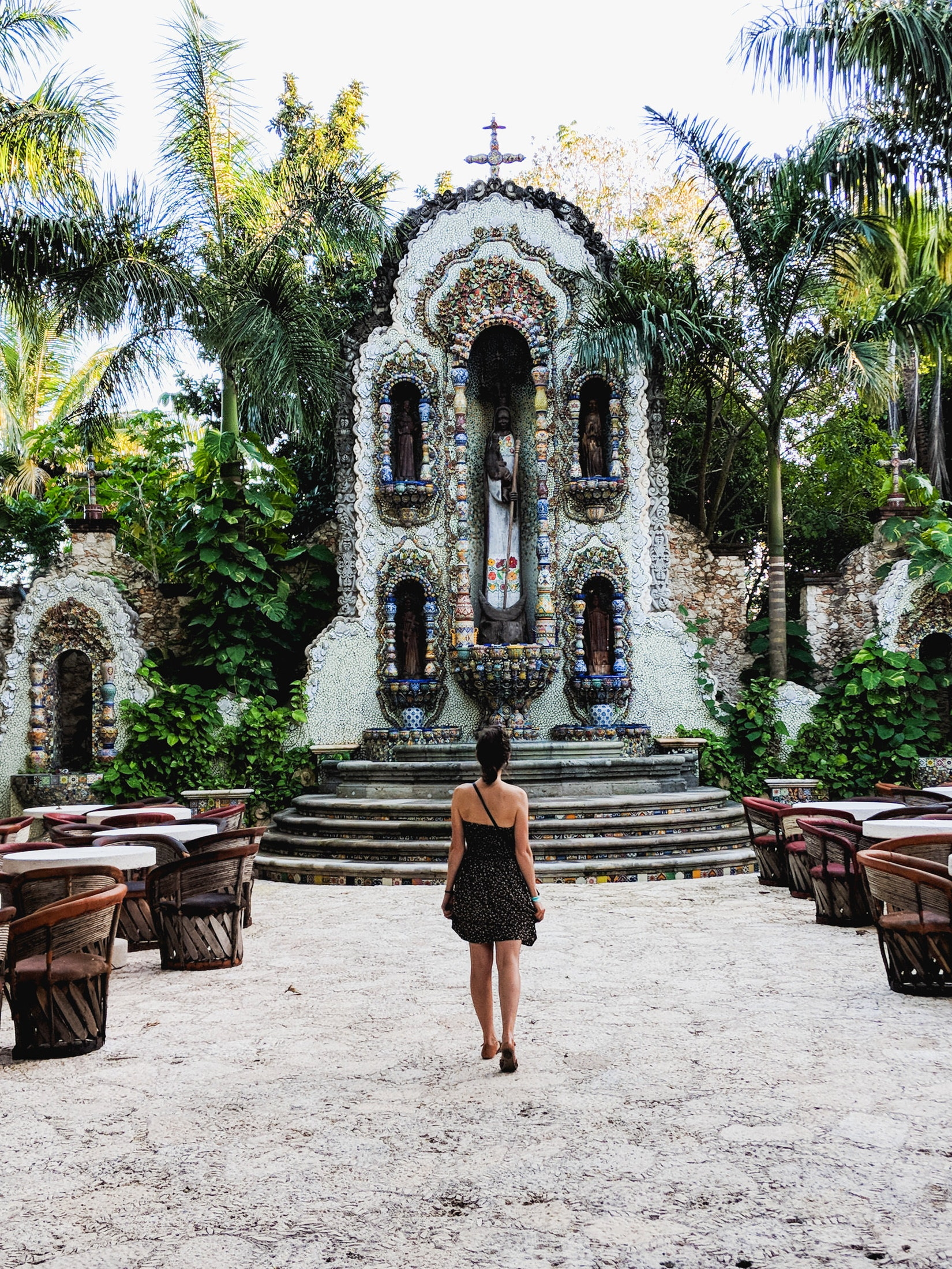 Becca walking in front of a colorful fountain in Valladolid, Mexico