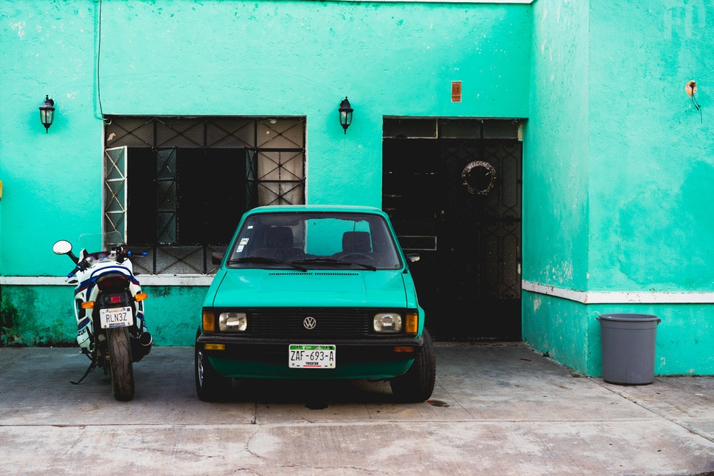 Teal and green wall behind a vintage car and motorcycle