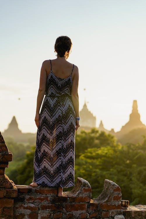 Kız ayakta pagodaların gün doğumu görünümüne bakıyor Bagan Myanmar Burma