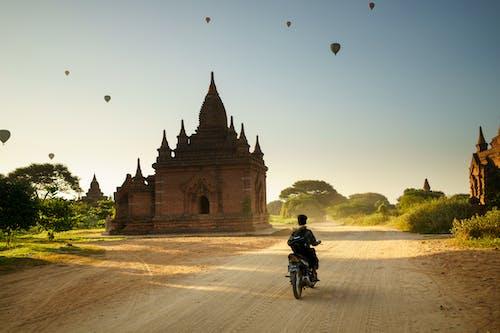 İki pagoda gündoğumu arasında moto kullanan adam Bagan Myanmar Burma