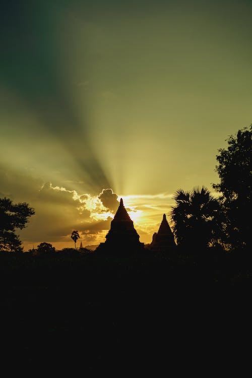 Gün batımında bir stupa yakınında bulutların arasından gelen güneş Bagan Myanmar Burma