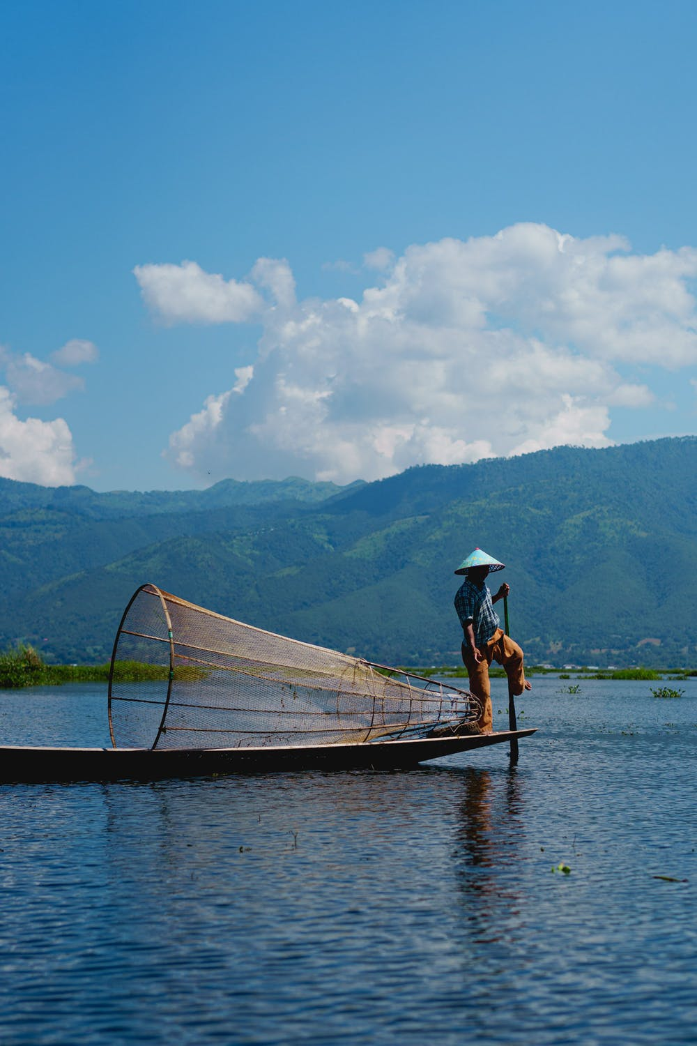 Burmese dancing fishermen standing at one end of his boat on a clear sunny day at Inle Lake Myanmar