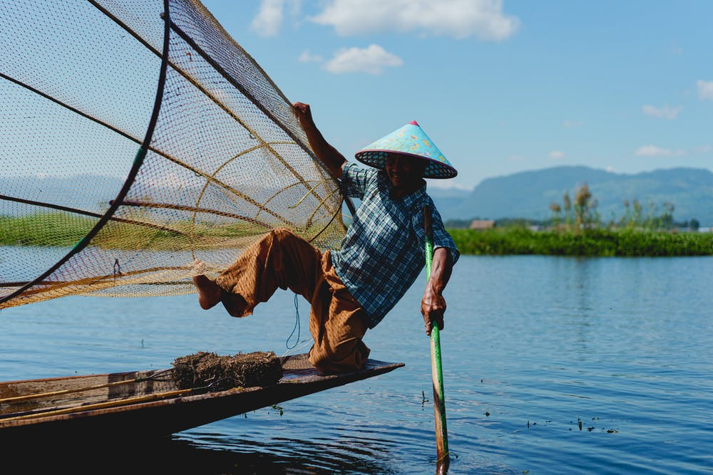 Burmese fisherman wearing a conical fishing hat posing for a photo with one leg up and balancing a fishing net
