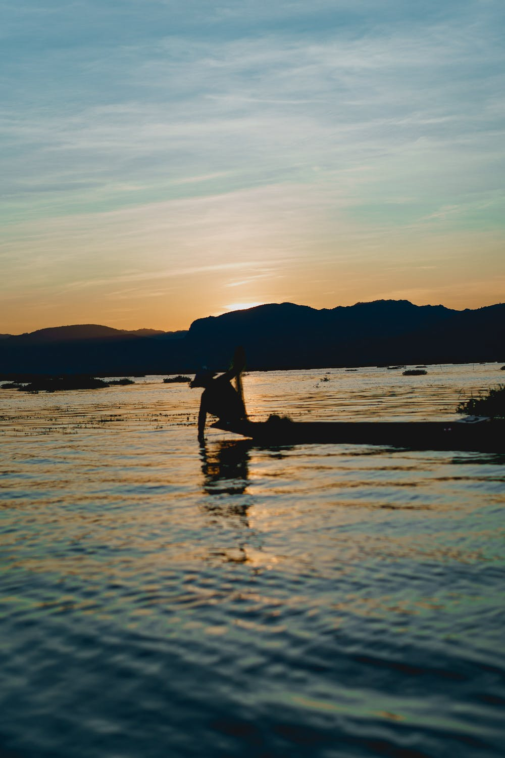 Burmese fisherman padding in his boat at sunset with mountains in the scenery at Inle Lake Myanmar