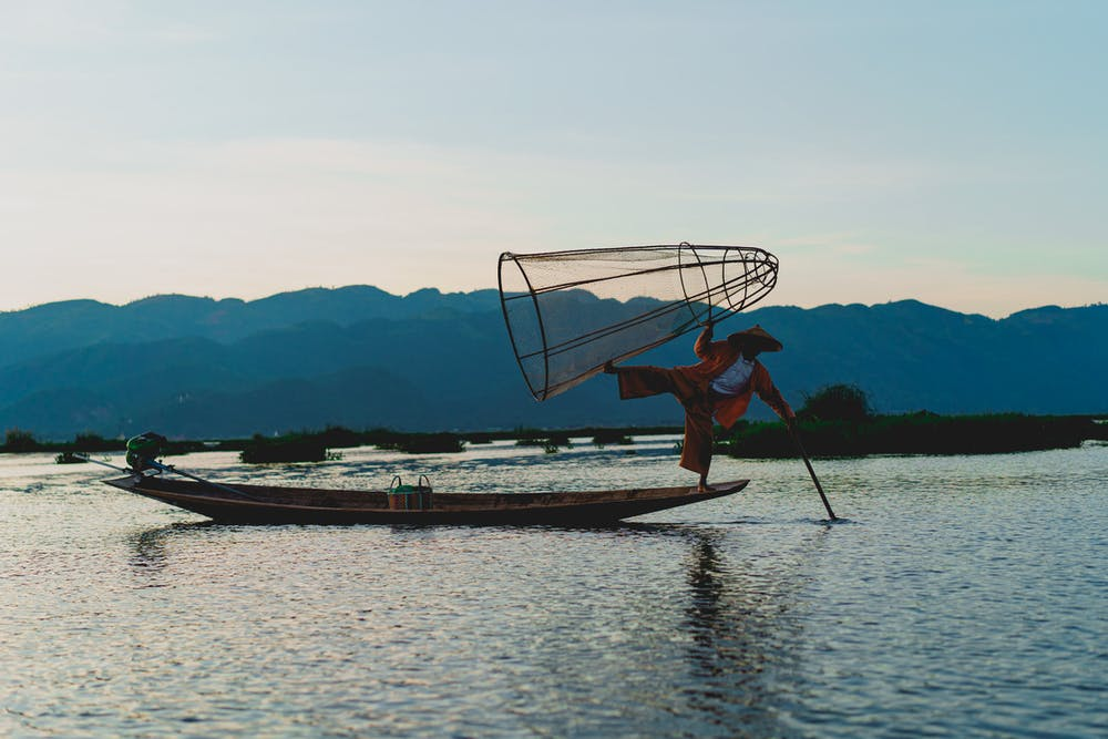 Inle Lake dancing fisherman balancing on a boat with one leg and holding a cone-shaped wood fishing net in Myanmar