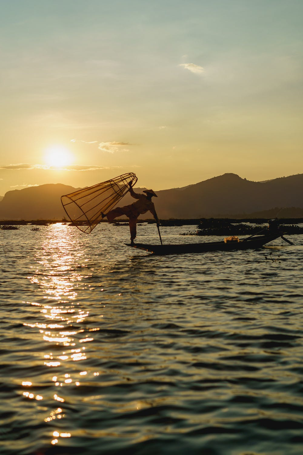 Famous dancing fisherman standing on one foot with fishing net during sunset golden hour scene at Inle Lake Myanmar
