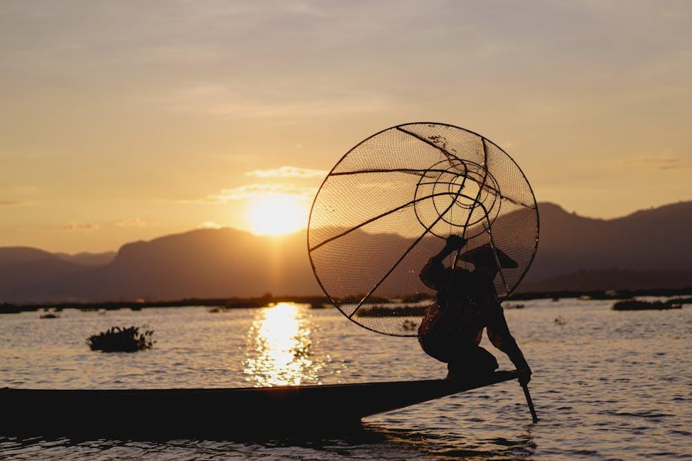 Burmese fisherman at Inle Lake holding up large conical fishing net during sunset mountain scenery in Myanmar
