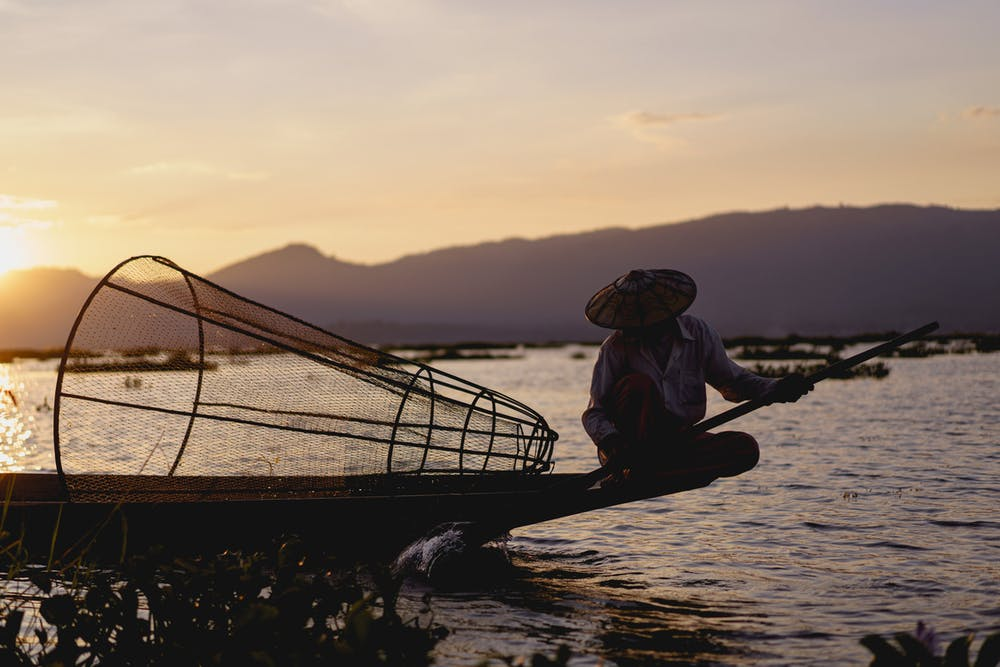 Burmese dancing fishermen sitting on the edge of a small fishing boat at sunset on Inle Lake