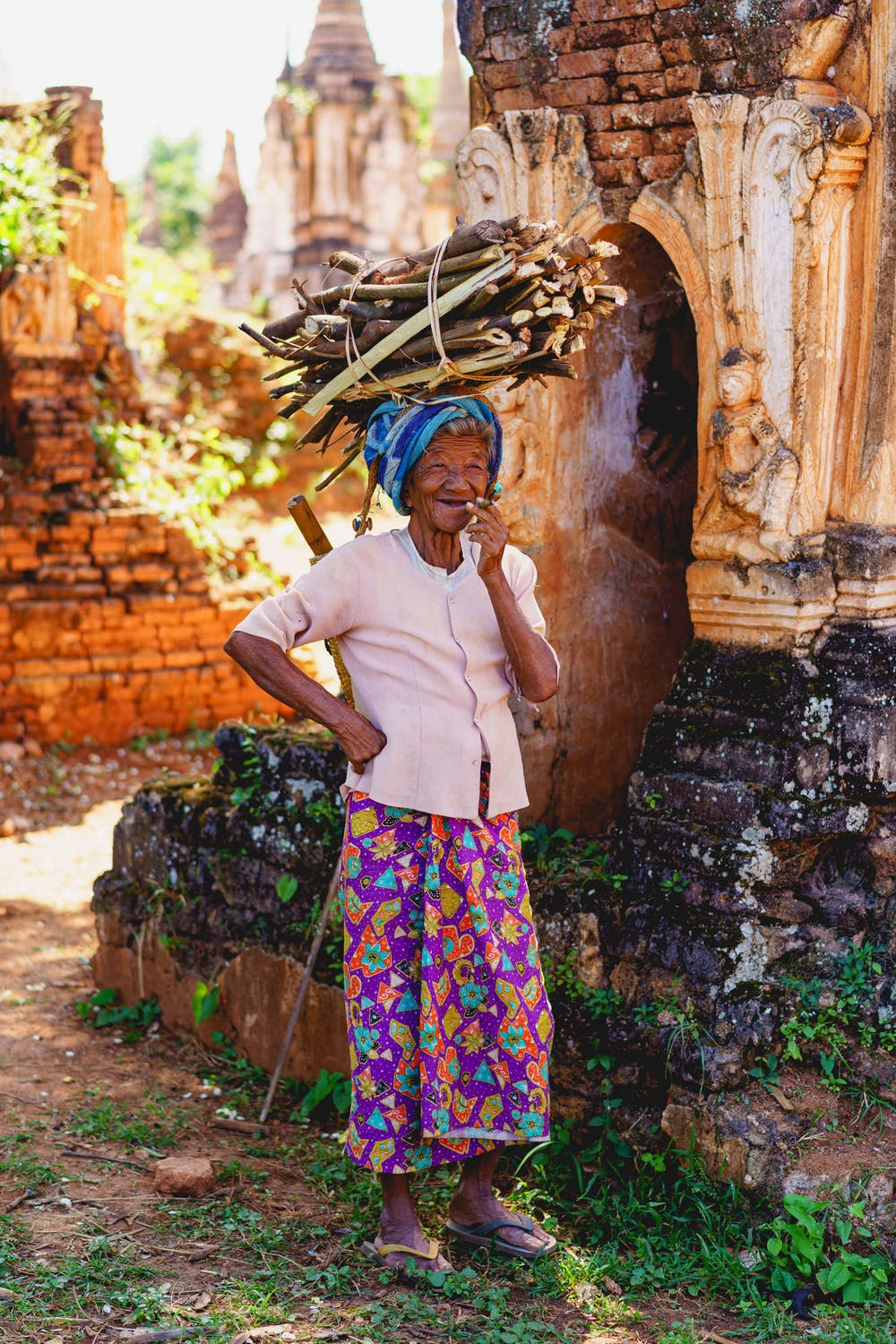 Portrait of an old Burmese ethnic minority tribal woman in a field of ancient stupas in Indein Myanmar