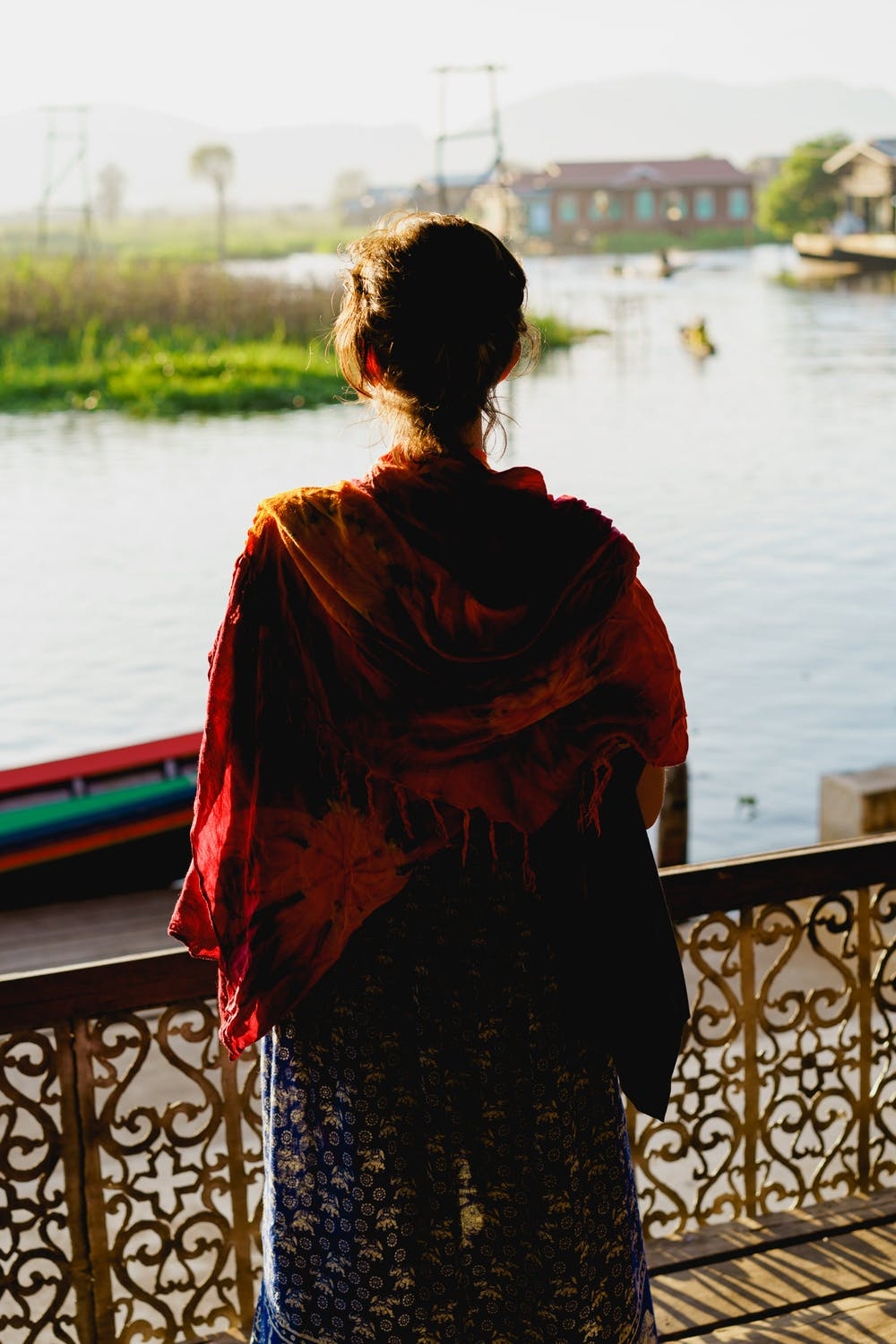 Girl wearing a red sarong looking at the waterway roads of the lake communities around Inle Lake Myanmar