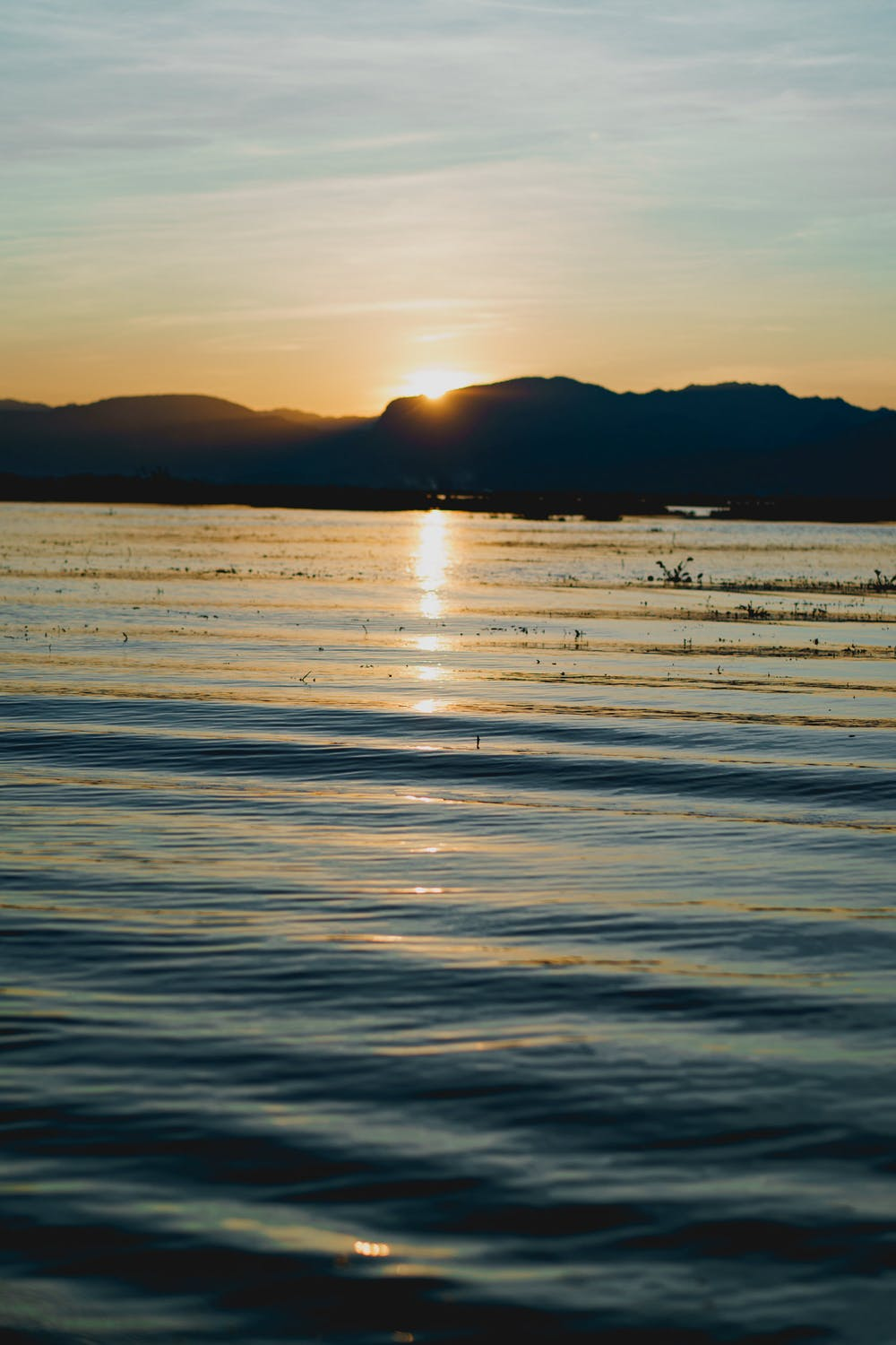 Sunset reflecting in the water along a mountain range at Inle Lake Myanmar