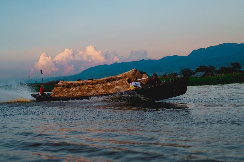 Two men drive a motorized motorboat full of wooden boxes along the waterways of Inle Lake Myanmar