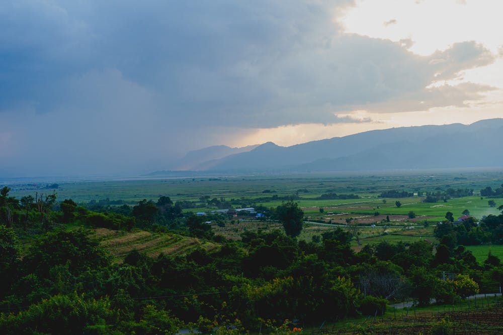 Rain clouds passing over mountains with farmland and fields below as seen from a hilltop near Inle Lake Myanmar