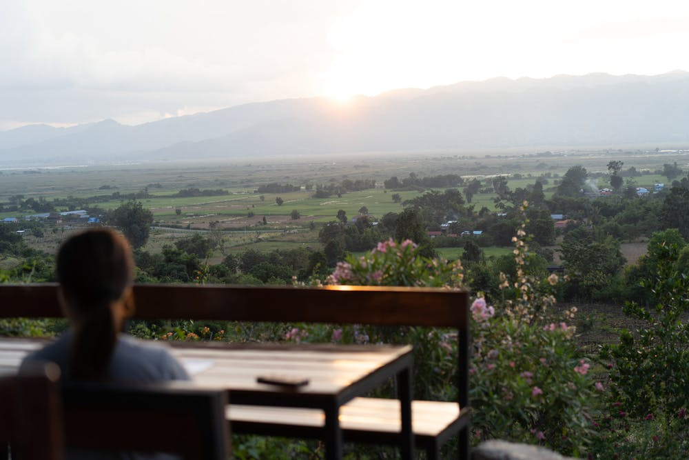 Travelers watch the sunset from wooden picnic tables at the Red Mountain Winery at Inle Lake Myanmar