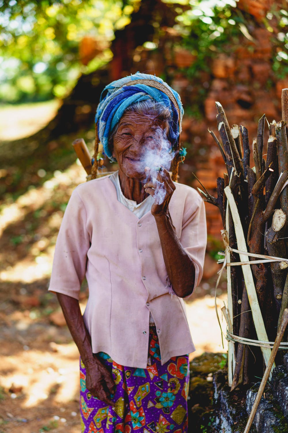 Portrait of an old Burmese ethnic minority tribal woman smoking a pipe and smiling in Indein Myanmar