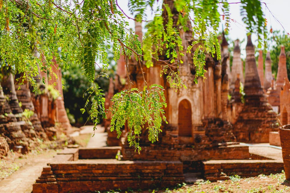 Green leaves in focus with ancient red stone pagodas and stupas at the Indein village in Myanmar