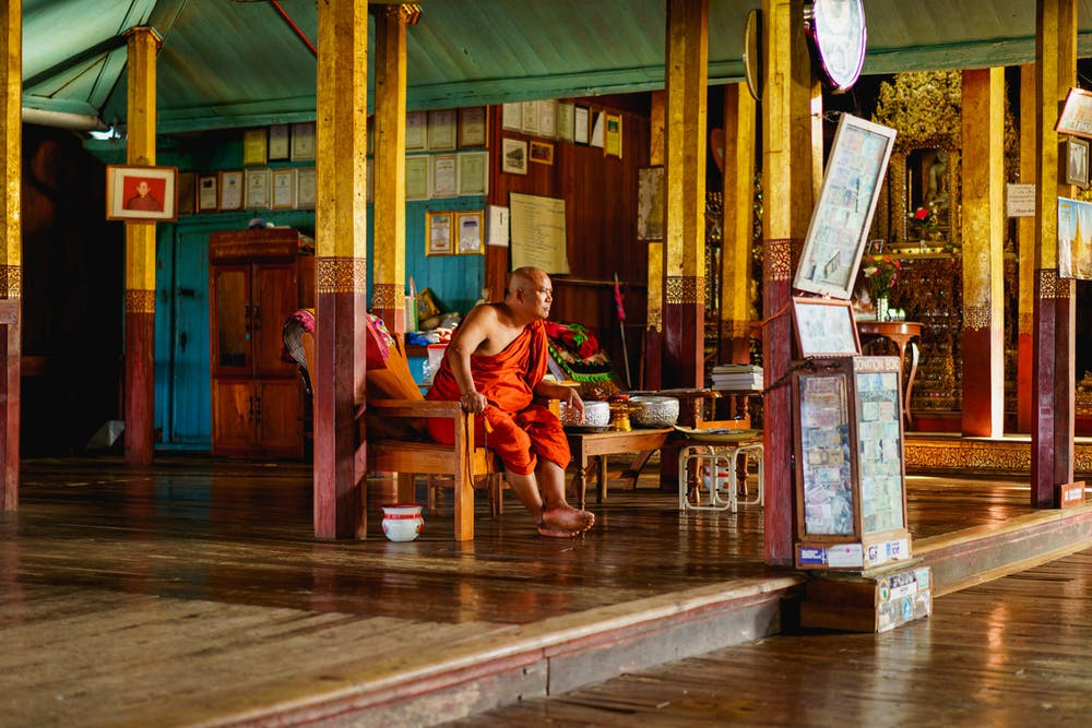 Male Buddhist monk sits in orange robes in an office at the Jumping Cat Monastery in Inle Lake Myanmar