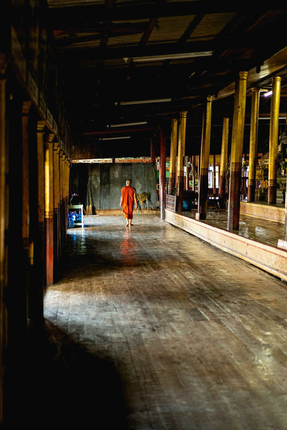 Buddhist monk in robes walking down a long hallway at Jumping Cat Monastery in Inle Lake Myanmar