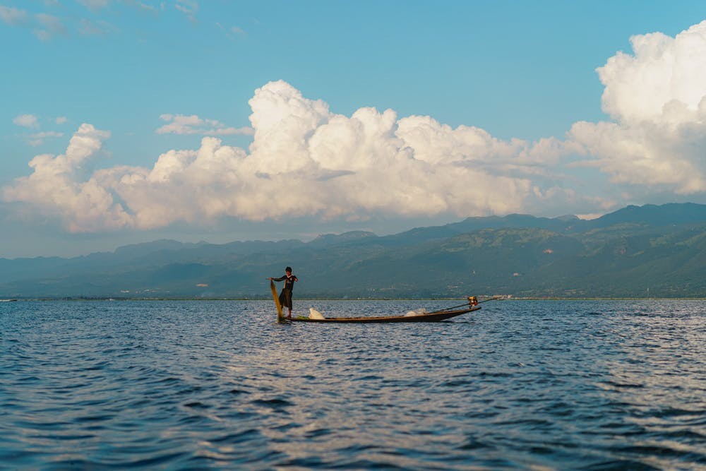 Young Burmese boy fishing from a wooden boat on a sunny clear day at Inle Lake Myanmar