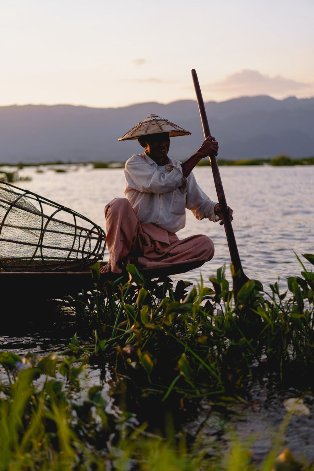 Inle Lake dancing fisherman sitting in a traditional Burmese fishing boat smiling at sunset in Myanmar
